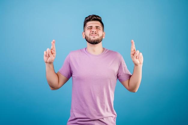 Jonge knappe mens die met gekruiste vingers bidden hopend op geluk geïsoleerd op blauw