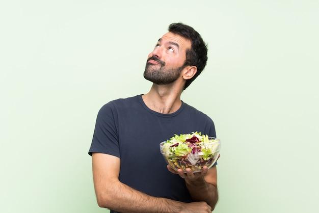 Jonge knappe mens die met salade over geïsoleerde groene muur omhoog terwijl het glimlachen kijkt