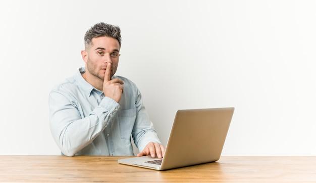 Jonge knappe mens die met zijn laptop werkt die een geheim houdt of om stilte vraagt.