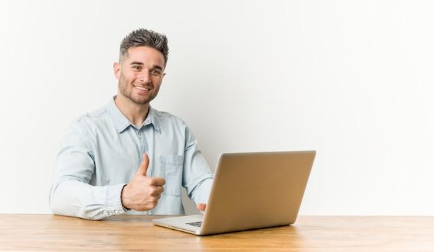 Jonge knappe mens die met zijn laptop werkt die en duim glimlacht opheft
