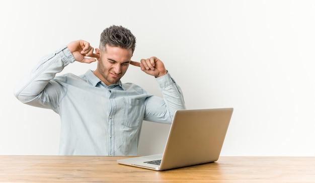 Jonge knappe mens die met zijn laptop werkt die oren behandelt met handen.