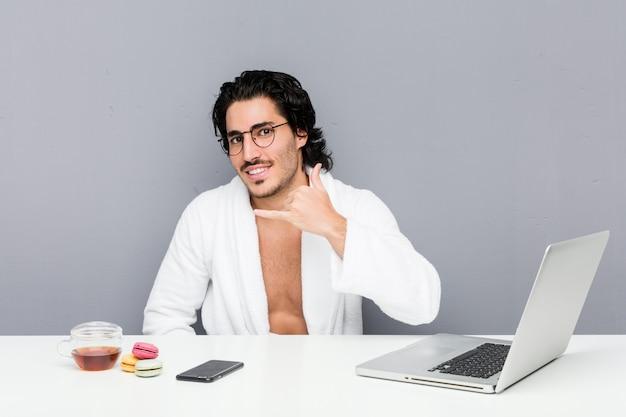 Jonge knappe mens die na een douche werkt die een mobiel telefoongesprekgebaar met vingers toont.