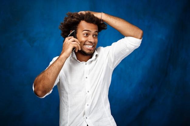 Jonge knappe mens die op telefoon over blauwe oppervlakte spreekt
