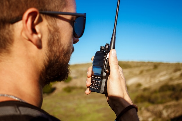 Jonge knappe mens die op walkie-talkieradio spreekt, die canion van mening geniet