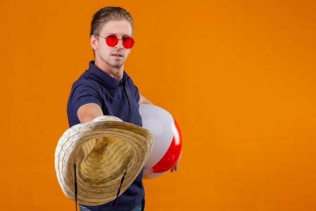 Jonge knappe mens die rode zonnebril dragen die opblaasbare bal houden en strohoeden met zekere uitdrukking uitrekken die zich over oranje achtergrond bevinden
