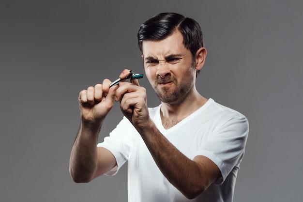Jonge knappe mens die scheerapparaat over grijze muur probeert te breken