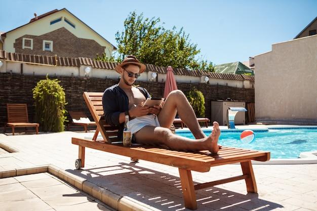 Jonge knappe mens die tablet bekijken, die dichtbij zwembad zitten