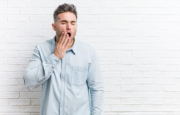 Jonge knappe mens die tegen bakstenen muur een vermoeid gebaar tonen die mond behandelen met hand