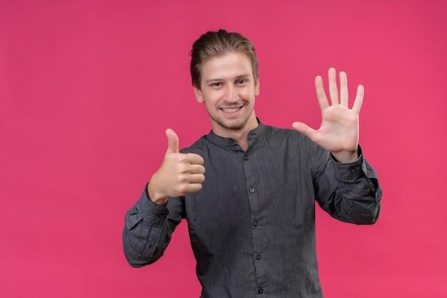 Jonge knappe mens die tonen en met vingers nummer zes glimlacht die zich over roze muur bevinden