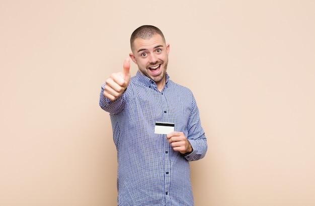 Jonge knappe mens die trots, zorgeloos, zelfverzekerd en gelukkig voelt, positief glimlachend met duimen omhoog met een creditcard