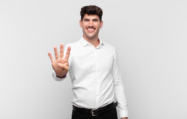 Jonge knappe mens die vriendelijk glimlacht kijkt, nummer vier of vierde met vooruit hand toont