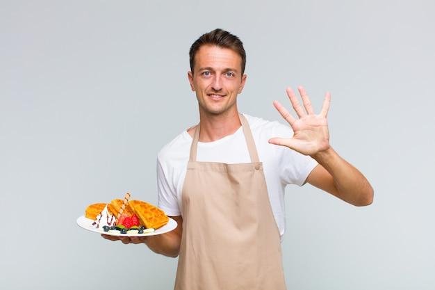 Jonge knappe mens die vriendelijk glimlacht kijkt, nummer vijf of vijfde met vooruit hand toont, aftellend