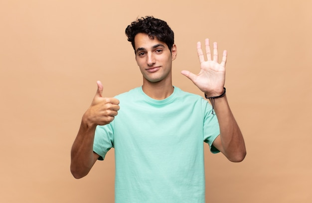 Jonge knappe mens die vriendelijk glimlacht kijkt, nummer zes of zesde met vooruit hand toont, aftellend