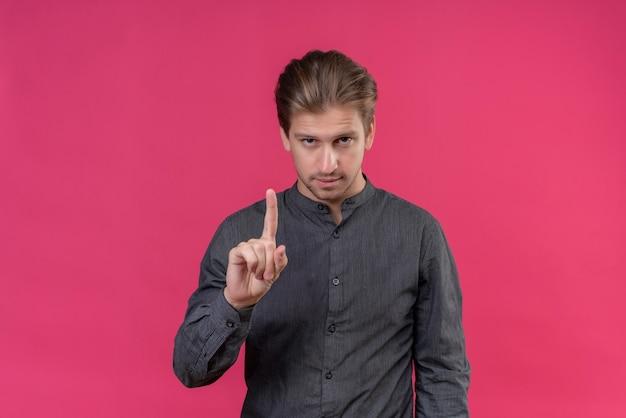 Jonge knappe mens die wijsvinger toont die met zelfverzekerde uitdrukking vraagt te wachten die zich over roze muur bevindt