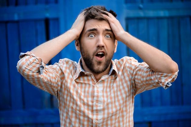 Jonge knappe mens in zenuwachtig plaidoverhemd
