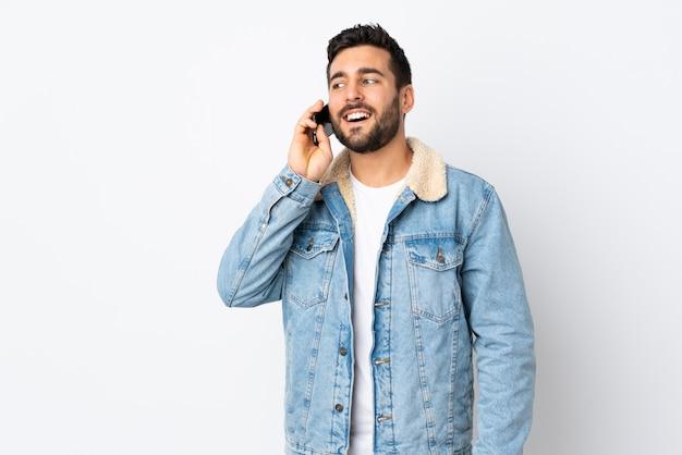 Jonge knappe mens met baard die op witte muur wordt geïsoleerd die een gesprek met de mobiele telefoon houdt
