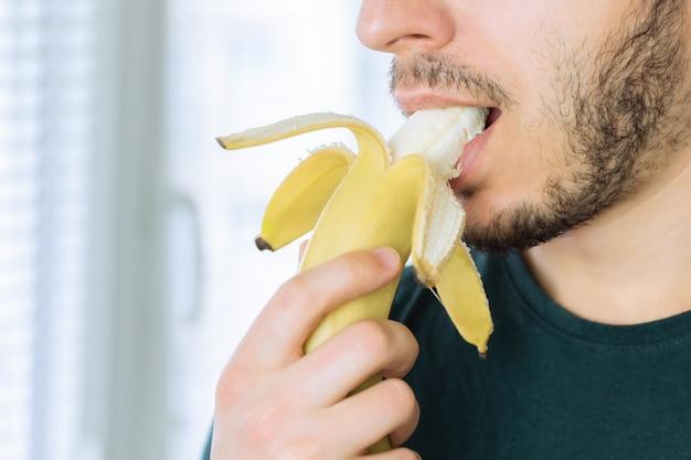Jonge knappe mens met een baard die van een banaan bijt die zich in keuken bevindt.