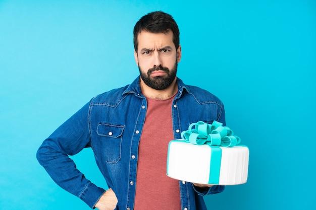 Jonge knappe mens met een grote cake over geïsoleerde blauwe boze muur