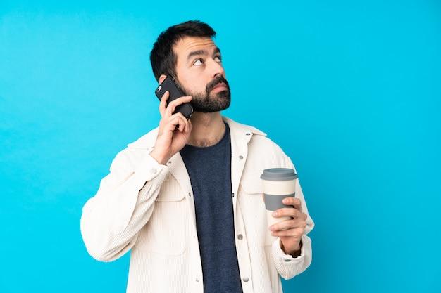 Jonge knappe mens met wit corduroy jasje over de geïsoleerde blauwe weg te halen koffie van de muurholding en mobiel