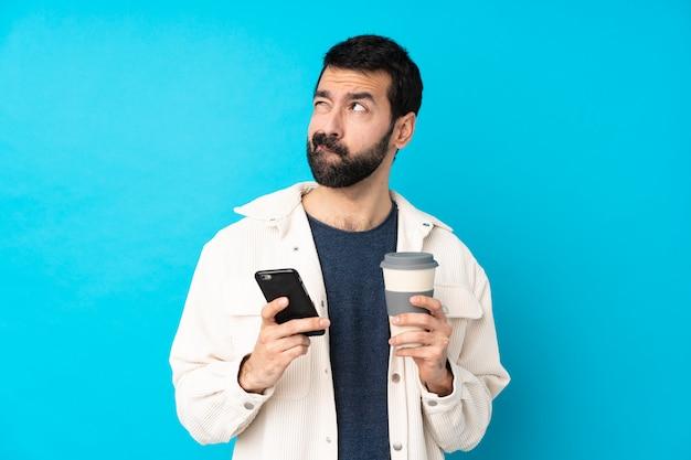 Jonge knappe mens met wit corduroy jasje over de geïsoleerde blauwe weg te nemen koffie van de muurholding en mobiel terwijl het denken van iets