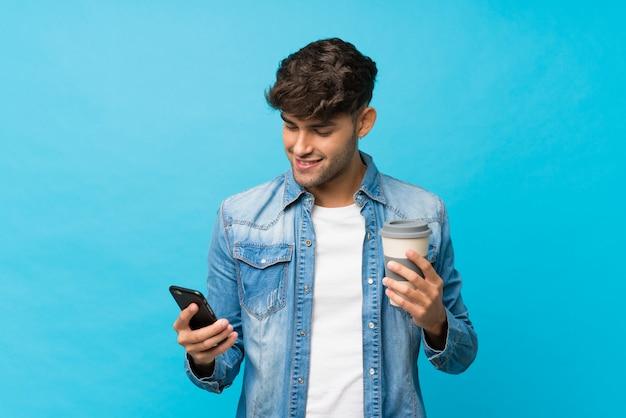 Jonge knappe mens over geïsoleerde blauwe weg te halen koffie van de muurholding en mobiel