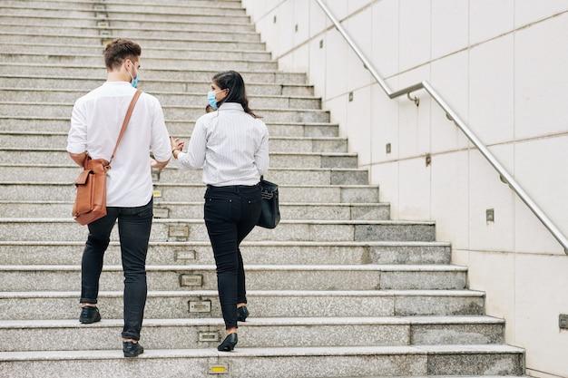 Jonge knappe mensen met medische maskers lopen de trap op en bespreken projecten waar ze samen aan werken
