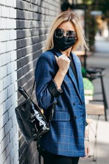 Jonge knappe mode vrouw in zonnebril met rugzak in gezichtsmasker vervuiling om zichzelf te beschermen tegen het coronavirus wandelen in de stad