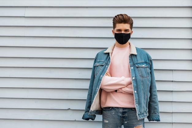 Jonge knappe modeman in denimblauwe modieuze kleding en met een gezichtsmasker om zichzelf te beschermen tegen coronavirus in de stad. stijlvol kerelmodel in jeugdjeansoutfit rust op straat in de buurt van muur.