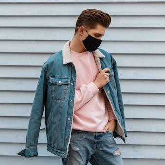 Jonge knappe modeman in denimblauwe modieuze kleding en met een gezichtsmasker om zichzelf te beschermen tegen het coronavirus in de stad. stijlvolle man in spijkerbroek rust op straat in de buurt van gebouw