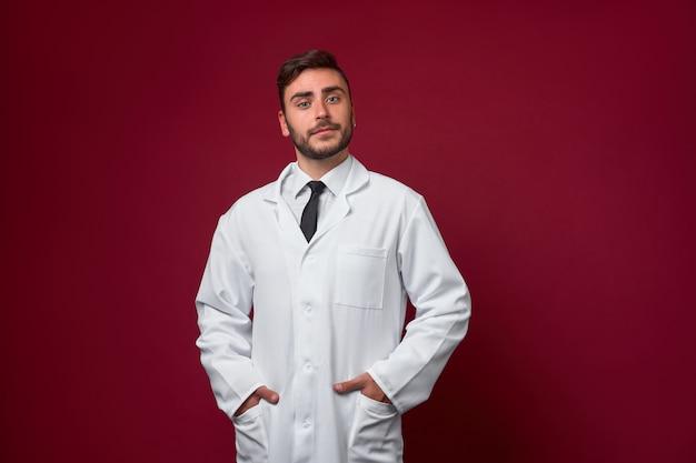 Jonge knappe moderne arts in een witte medische jurk staat in de studio op een rood