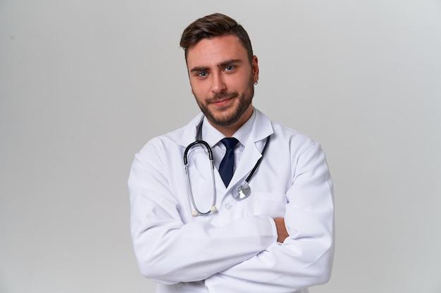 Jonge knappe moderne arts in een witte medische jurk staat in de studio op een wit. student-stagiair van een medische universiteit.