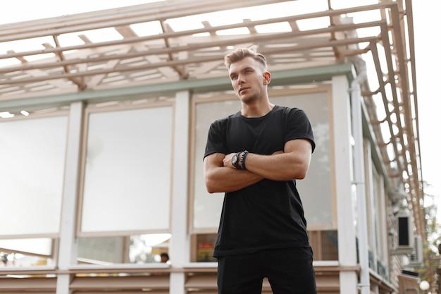 Jonge knappe modieuze amerikaanse model man met kapsel in zwart t-shirt op straat in de buurt van een houten gebouw
