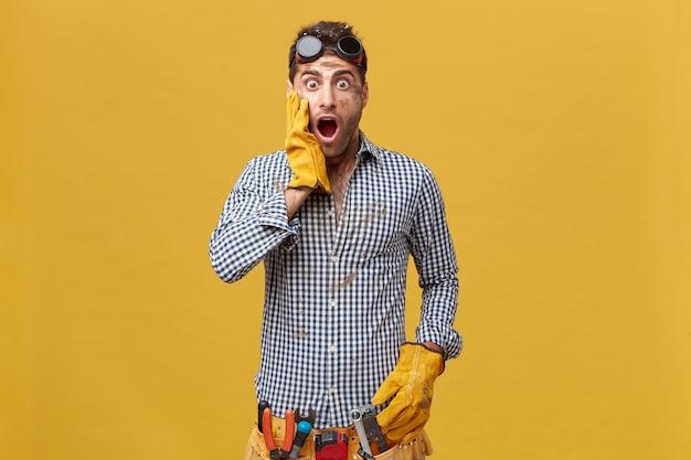 Jonge knappe monteur die beschermende kleding met riem van hulpmiddelen draagt die zijn hand in handschoenen op de wang houdt die met afgeluisterde ogen kijken en zijn mond opende die zijn fout realiseerde. werk concept