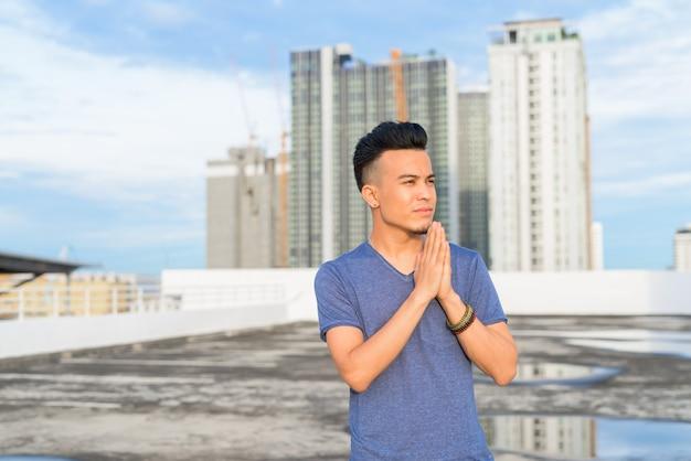 Jonge knappe multi-etnische man met handen samen tegen uitzicht over de stad