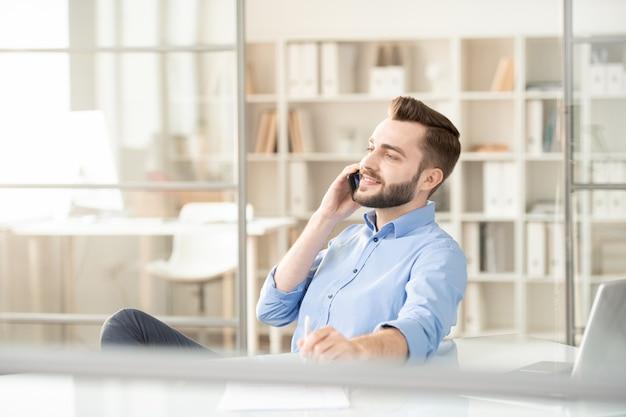 Jonge knappe officemanager of makelaar met mobiele telefoon die met cliënt communiceert zittend op de werkplek