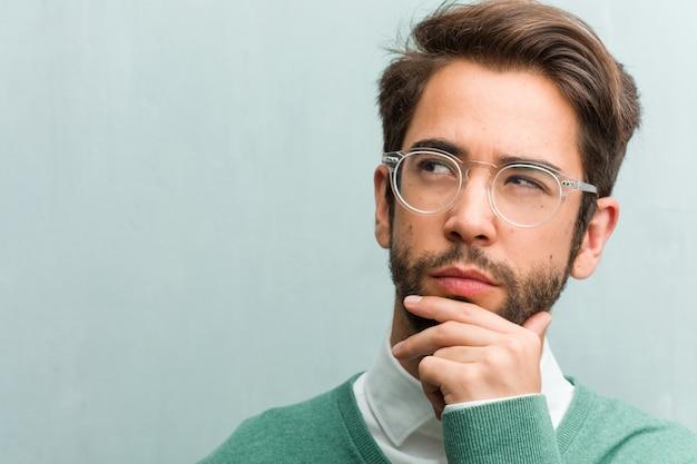 Jonge knappe ondernemer gezicht close-up twijfelen en verward, denken aan een idee of bezorgd over iets