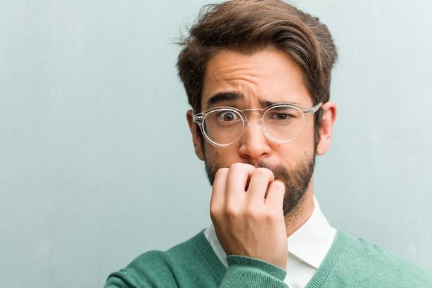 Jonge knappe ondernemer man gezicht close-up bijten nagels, nerveus en zeer angstig en bang voor de toekomst, voelt paniek en stress