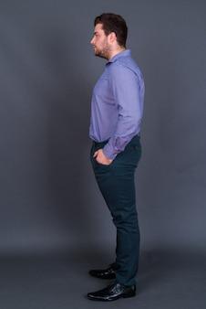 Jonge knappe overgewicht bebaarde zakenman op grijs