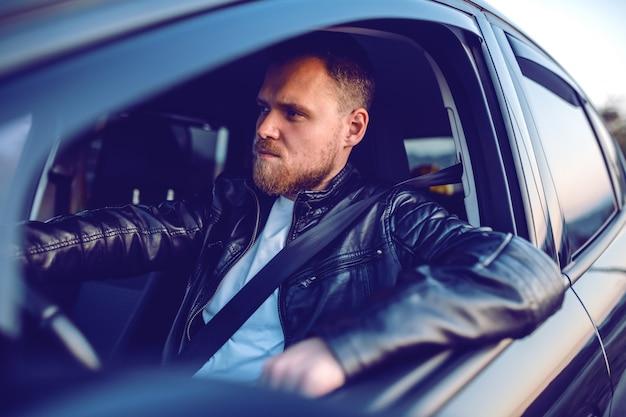 Jonge knappe peinzende bebaarde blonde blanke man in lederen jas poseren in zijn moderne auto.