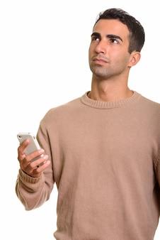 Jonge knappe perzische man met behulp van mobiele telefoon tijdens het denken