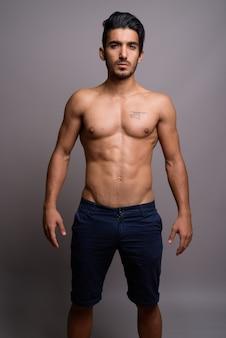 Jonge knappe perzische man shirtless tegen een grijze achtergrond