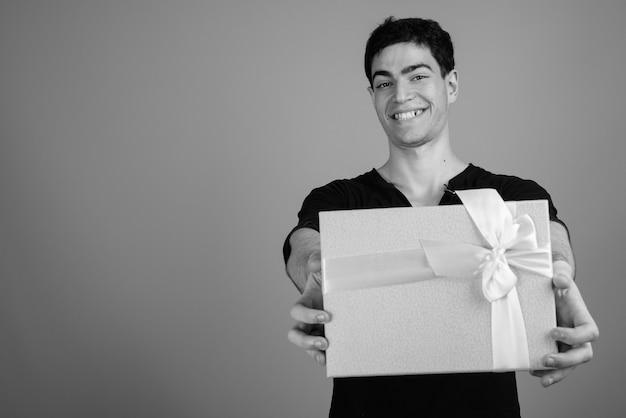 Jonge knappe perzische man tegen grijze muur in zwart-wit