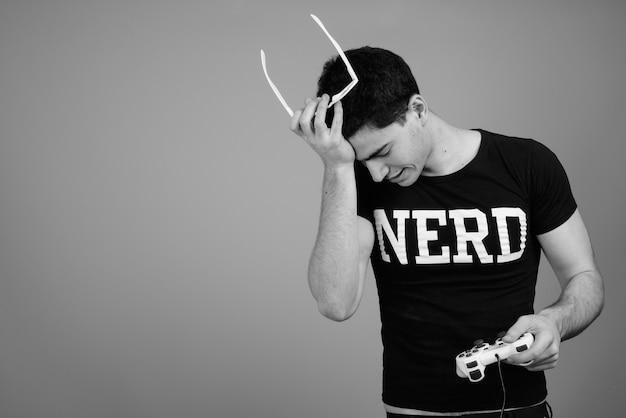 Jonge knappe perzische nerd man met bril tegen grijze muur in zwart-wit