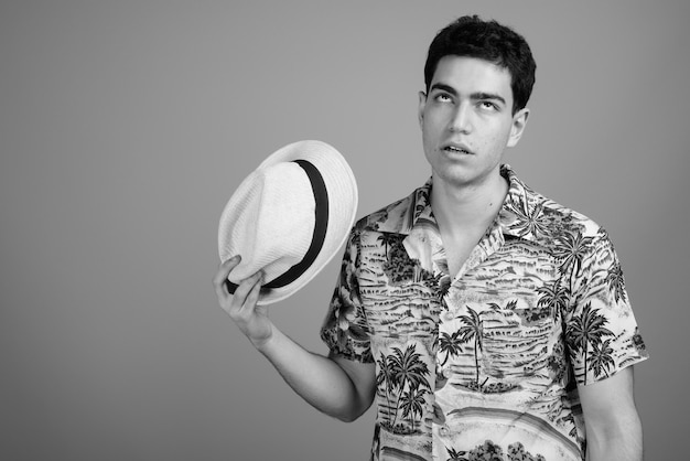 Jonge knappe perzische toeristenman met een hawaïaans shirt en hoed klaar voor vakantie in zwart-wit