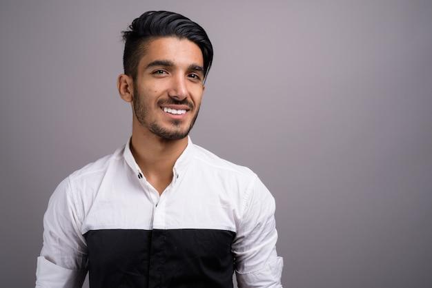 Jonge knappe perzische zakenman tegen grijze achtergrond