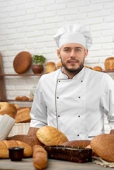 Jonge knappe professionele bakker die in zijn winkel werkt