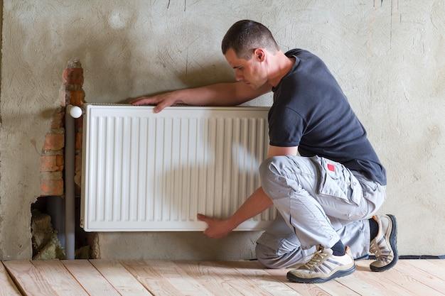 Jonge knappe professionele loodgieter werknemer verwarming radiator installeren in een lege ruimte van een nieuw gebouwde appartement of huis. concept van constructie, onderhoud en reparatie.