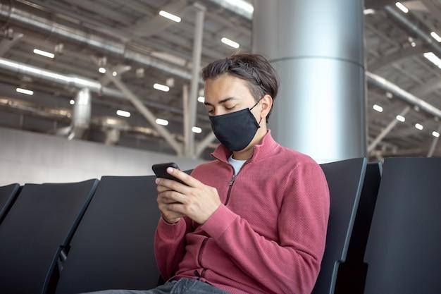 Jonge knappe reiziger in een masker in de lounge van de luchthaventerminal met smartphone-app in openbare wifi-ruimte, messaging