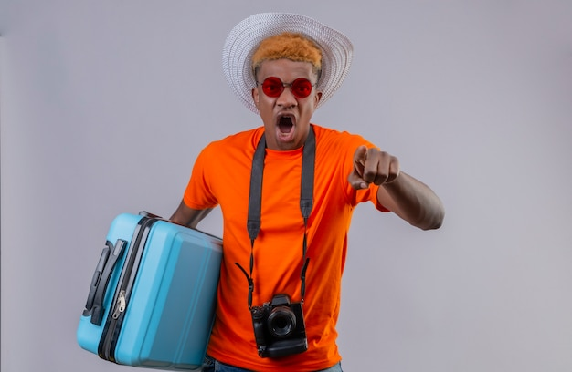 Jonge knappe reiziger jongen in zomer hoed dragen oranje t-shirt houden reiskoffer wijzend naar camera met vinger schreeuwen met boos gezicht