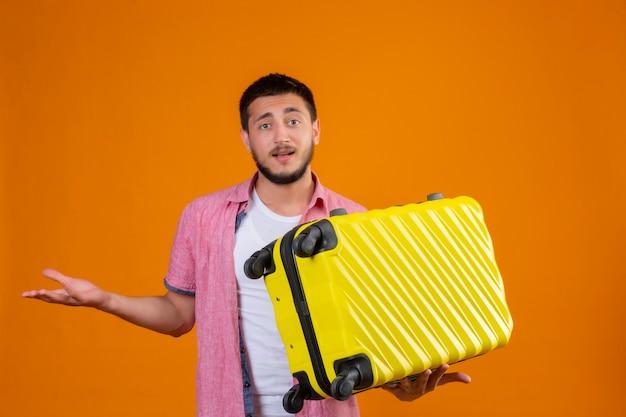 Jonge knappe reiziger kerel bedrijf koffer clueless en verward kijken camera staan met opgeheven arm twijfels over oranje achtergrond